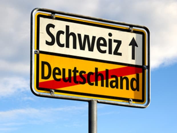 The picture shows a montage that reminds one of a town exit sign. Germany is crossed out as the end of the town and Switzerland is signposted as the entrance.
